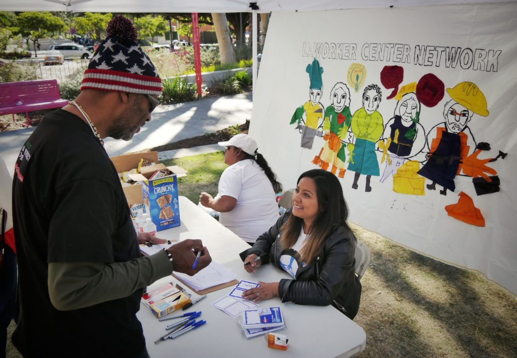 A worker checks in at the welcome booth for the LA Worker Center Network Resilience Fair.
